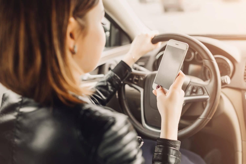 Eine Frau sitzt im Auto und benutzt ihr Smartphone. Foto: deineka